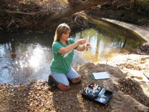 Lisa Pippin-Hall measuring hardness in a stream near Smiths Station
