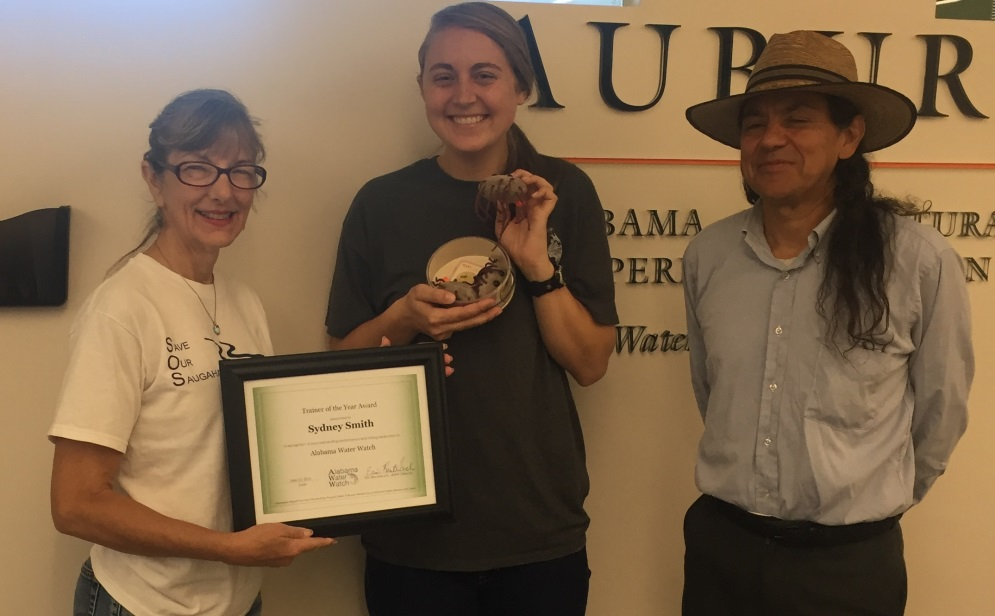 """Sydney receives her certificate and an extra special gift – a petri dish full of E. coli (don't worry they were just cute stuffed replicas. """"AWW workshops have been multiplying like E. coli since Sydney came on board as a trainer!"""" – Director of AWW, Eric Reutebuch."""