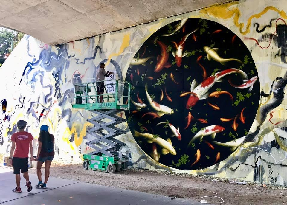 Muralist Brandon-Sadler paints under a bridge
