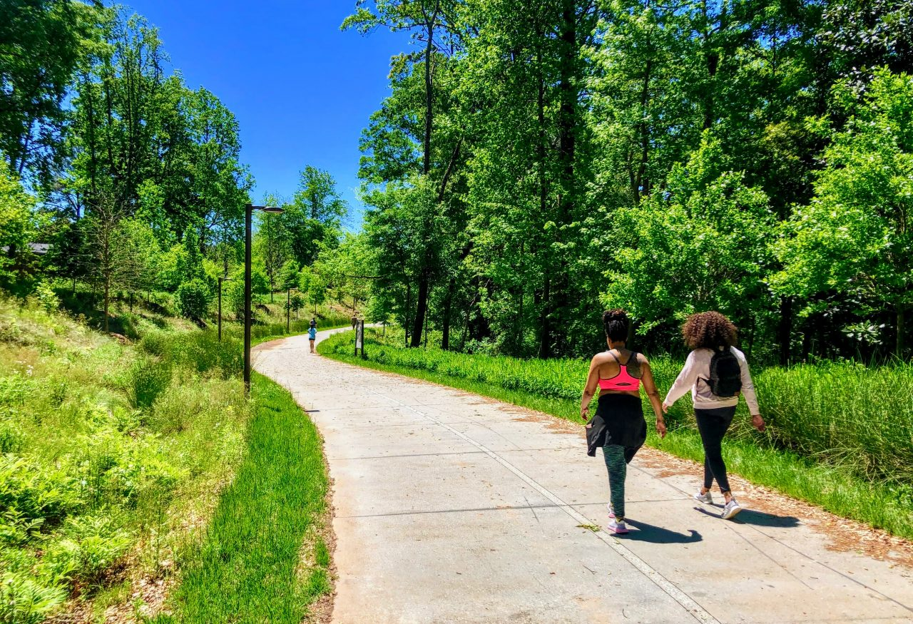 Two women walk on urban trail with trees