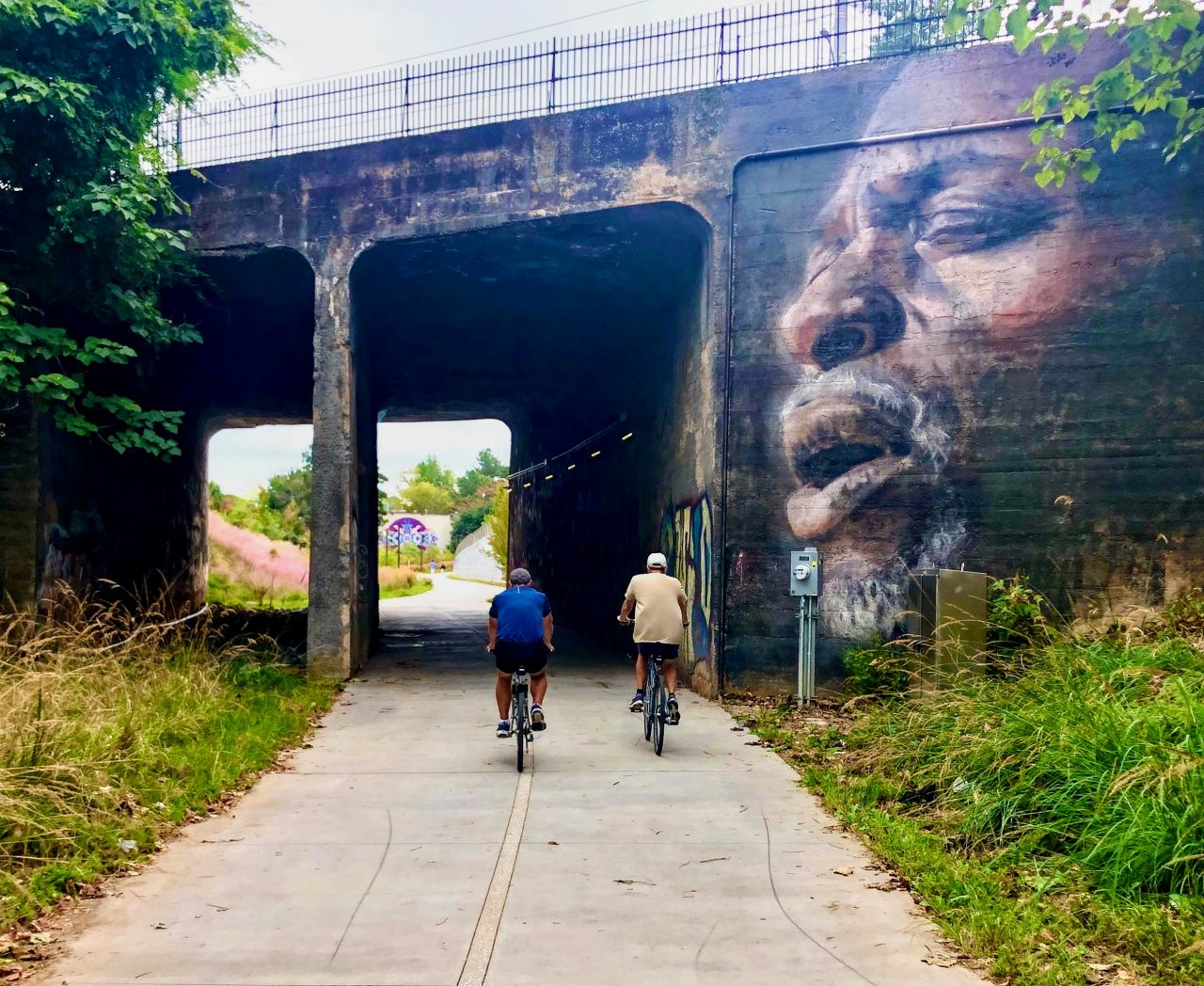 Bikers ride near mural underpass