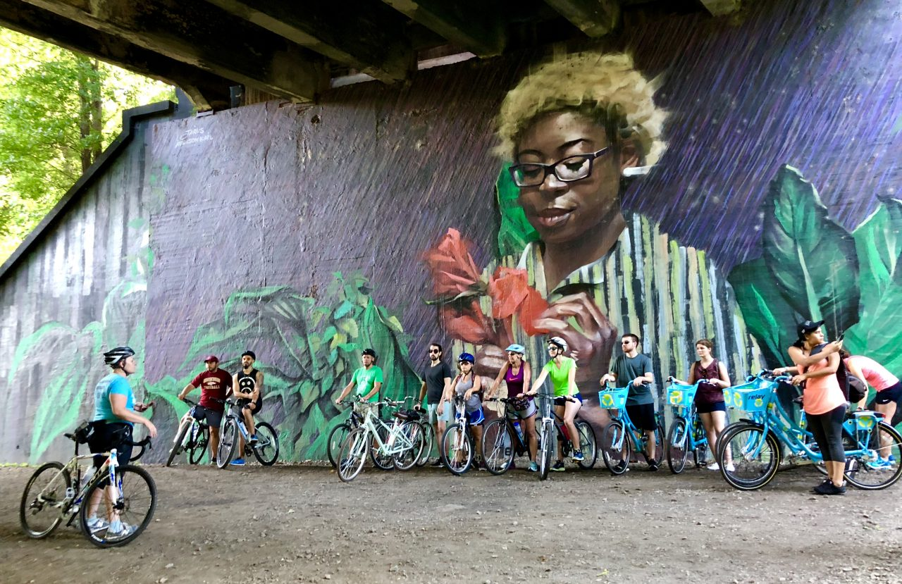Bikers prepare for ride under a mural-covered underpass