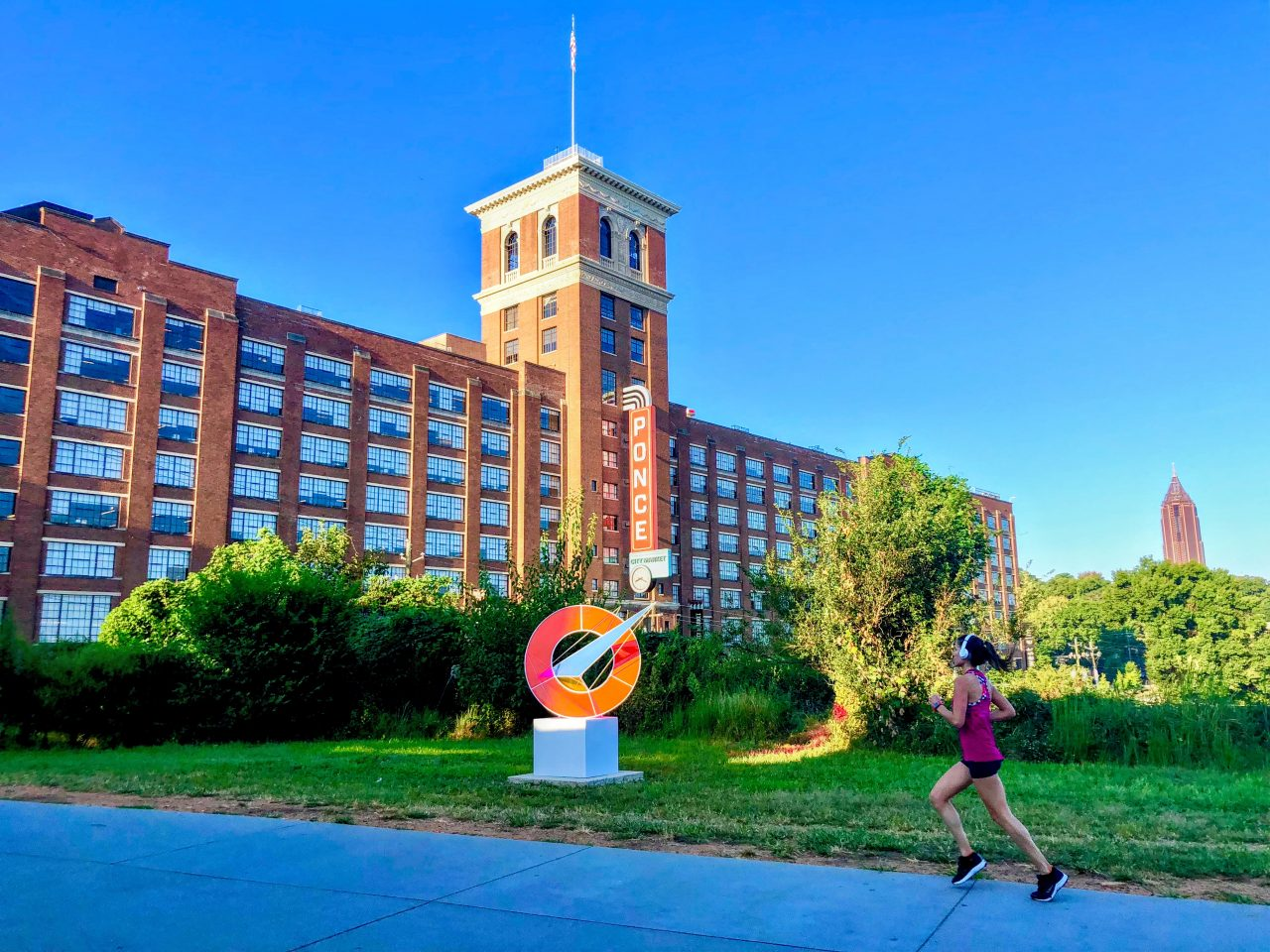 Woman jogs near Ponce City Market building
