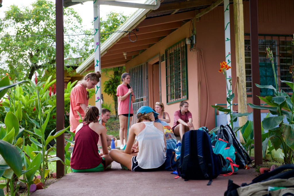 Students sit in a circle to rest after painting the outside of a school house in Costa Rica.