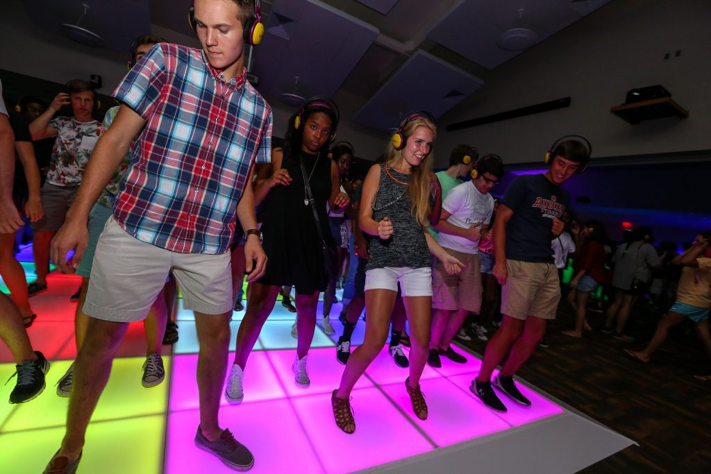 students shown dancing on a glowing dance floor.