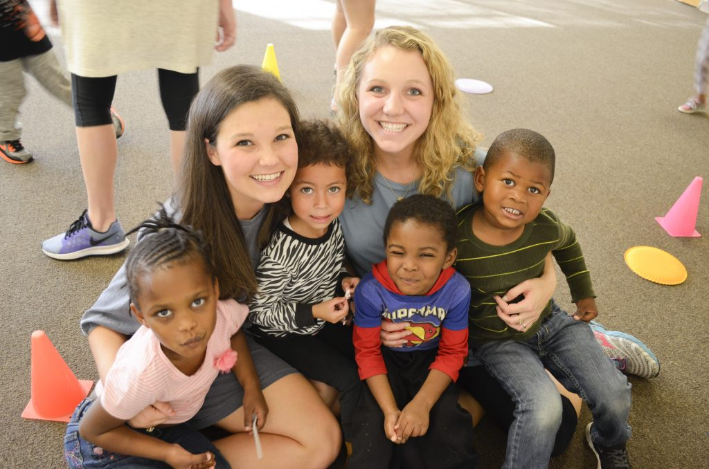 Two students pictured with little kids while serving at a day care.