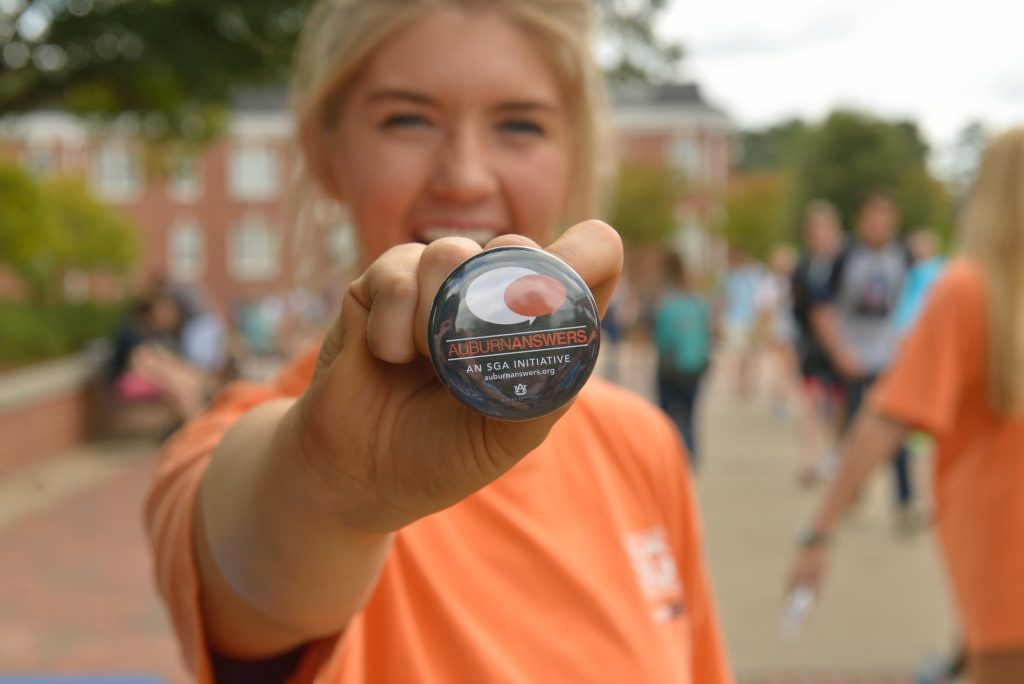 A student is pictured holding an Auburn Answers button while standing on the concourse.