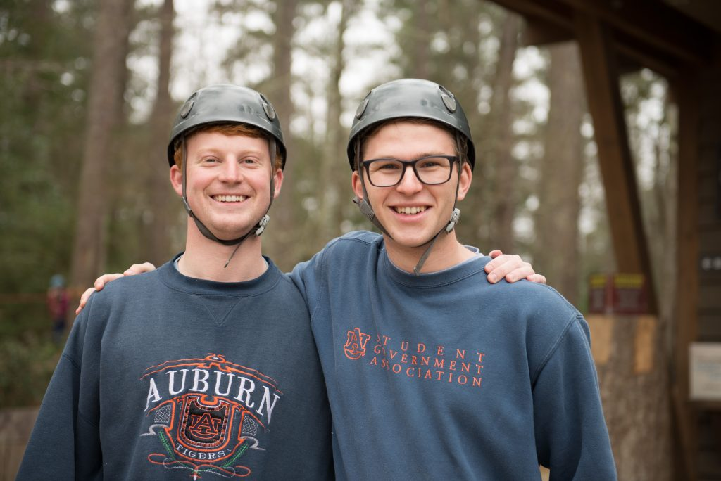 A photo of two men wearing helmets outside a ropes course.