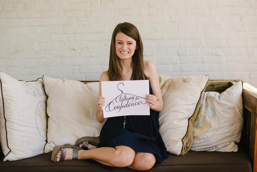 A photo of Madison Rolling, Miss Auburn, seated on a sofa holding a Clothing for Confidence sign.