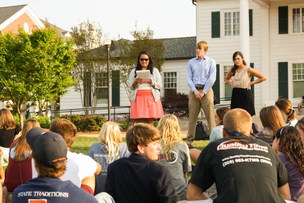 A photo of a three students leading a small group discussion.