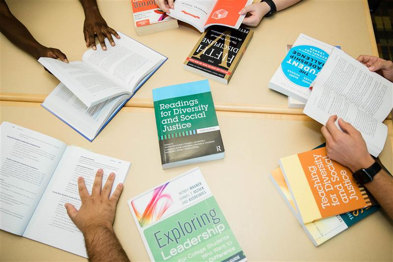 Diversity book with hands reaching for it on a table