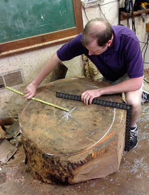 Third generation woodturner Matt Moulthrop of Atlanta measures a section of the College Street oak.