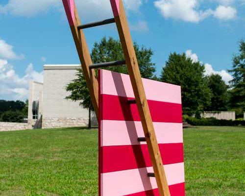 A wooden ladder intersecting a pink and red square
