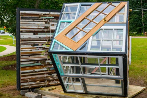 A house made from Old window frames, wood, and sheet glass