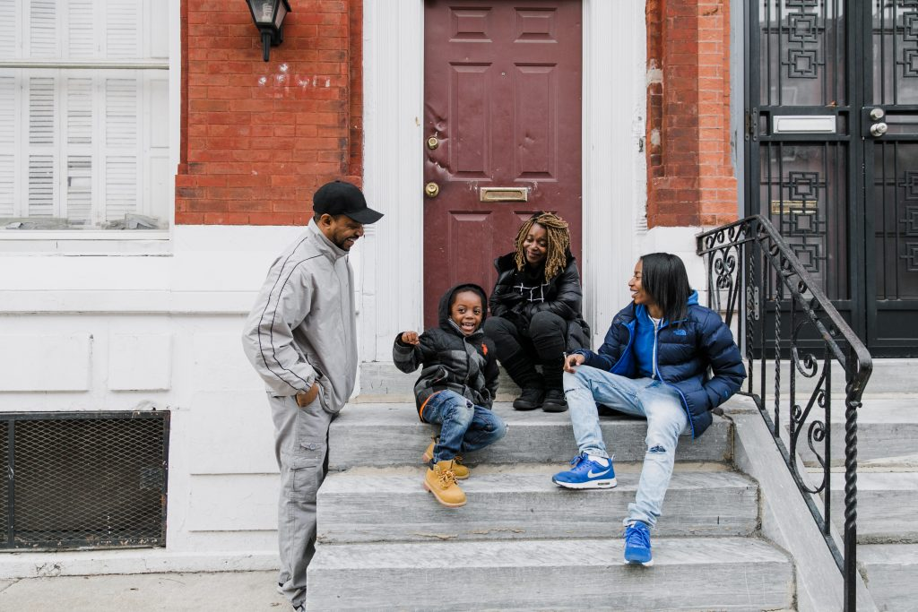 "Christopher ""Quest"" Rainey, Isaiah Byrd, Christine'a ""Ma Quest"" Rainey, Patricia ""PJ"" Rainey sit on a stoop. Credit: Carina Romano"