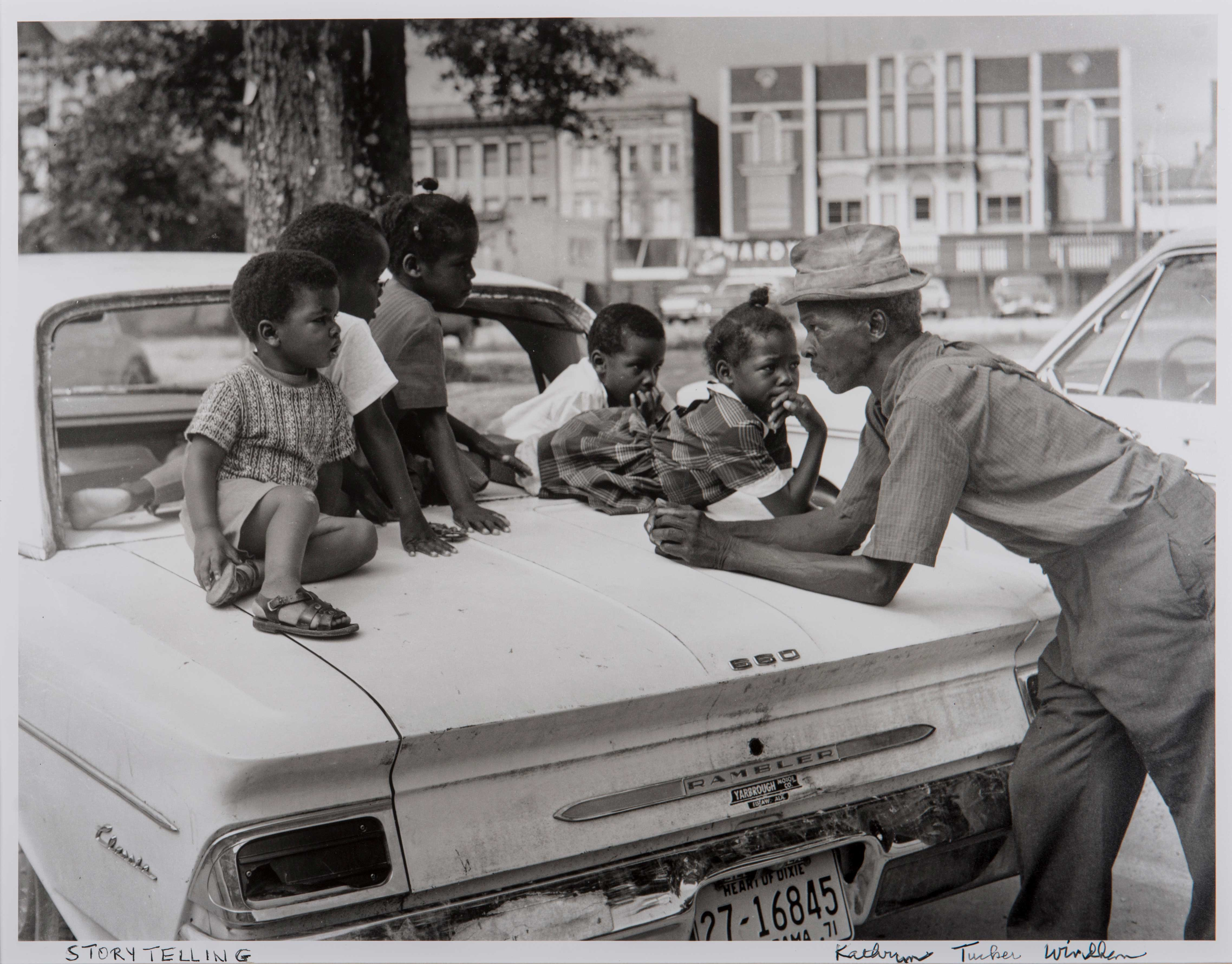 A group of boys and girls sit on a car hood and listen to a man.