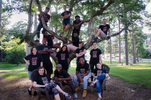 Members of Mosaic Theatre Company pose in a tree.