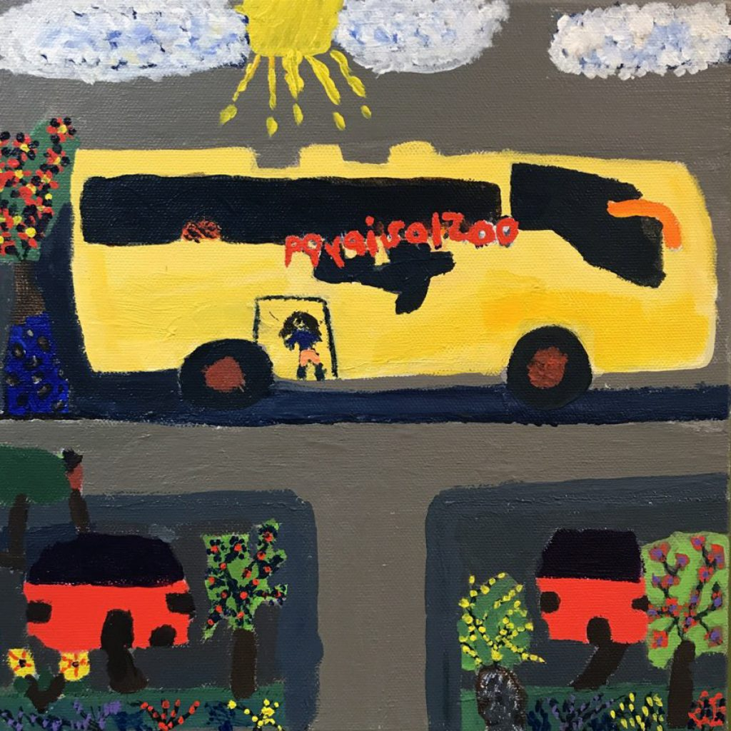 A large yellow bus drives down a road. There are two red buildings in the front with trees and flowers all around. A figure is in the luggage holding area of the bus.