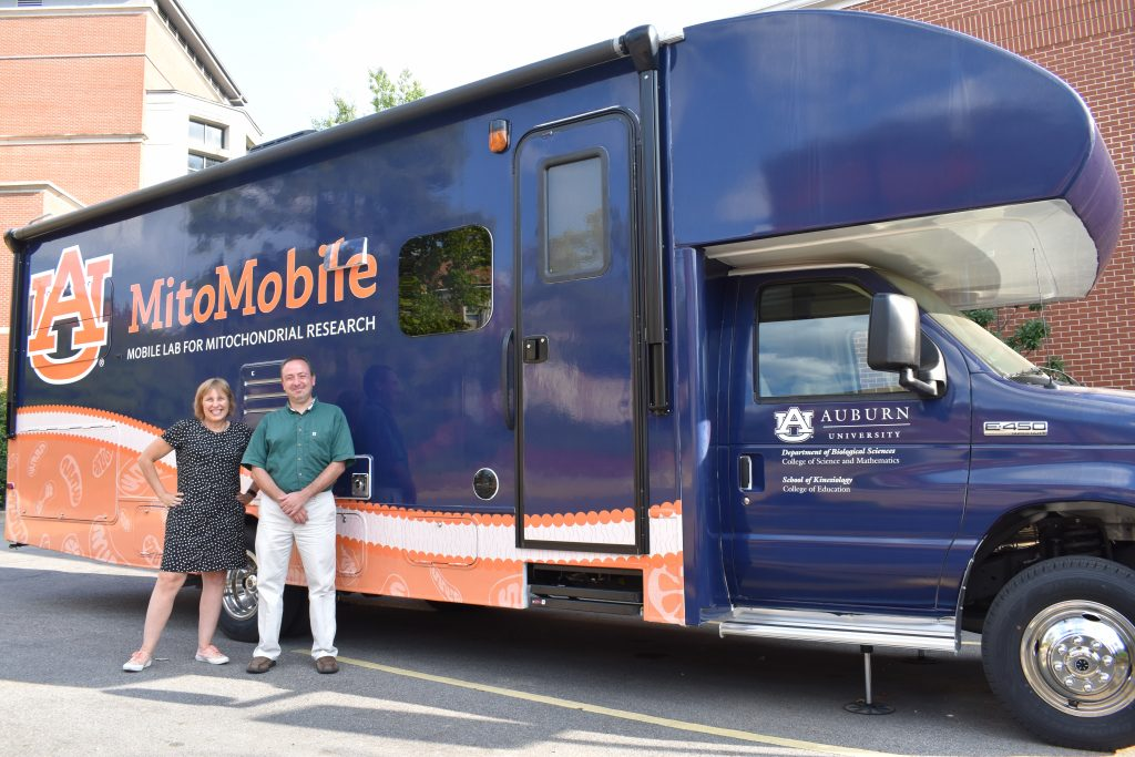 Photo of the MitoMobile - a lab on wheels that studies Mitochondria - with Wendy Hood and Andreas Kavazis standing in front