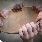 Wooden bowl held by numerous people's hands.